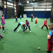 Coach Courtney teaches proper form during a U10 instructional clinic